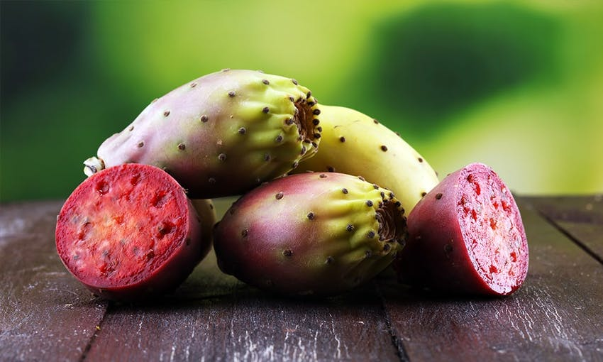 a pile of prickly pear cactus with two chopped in half to reveal pink and seeded inside
