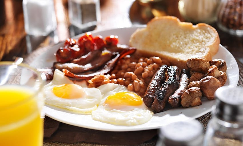 a full english breakfast consisting of a slice of white bread, fried mushrooms, three sausages, rashers of bacon, beans and two fried eggs with a glass of orange juice