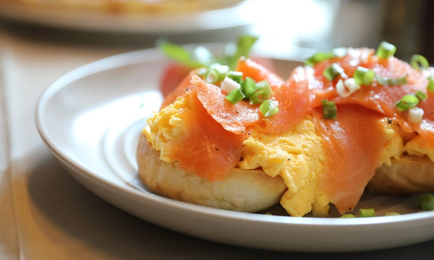 egg salmon and avocado bagel served on a white dish topped with diced spring onion