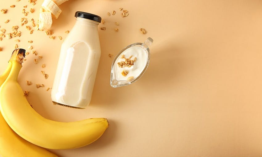 a bunch of bananas some sprinkled oats and a glass bottle of milk with a yellow background
