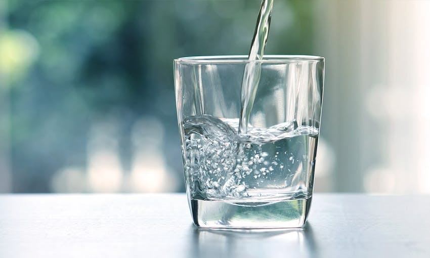 a glass of water on a tabletop with water being poured into it
