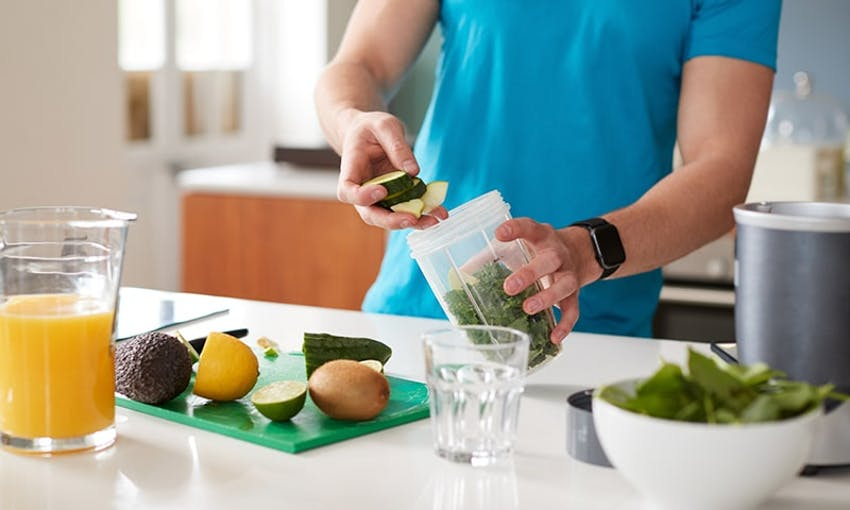 man in a blue tshirt adding healthy foods to a smoothie blender with some chopped fruits on chopping board and a glass of orange juice