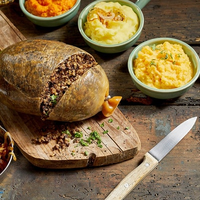 Haggis slightly chopped to reveal inside on a wooden chopping board surrounded by mini serving dishes of crispy onions, neeps and tatties