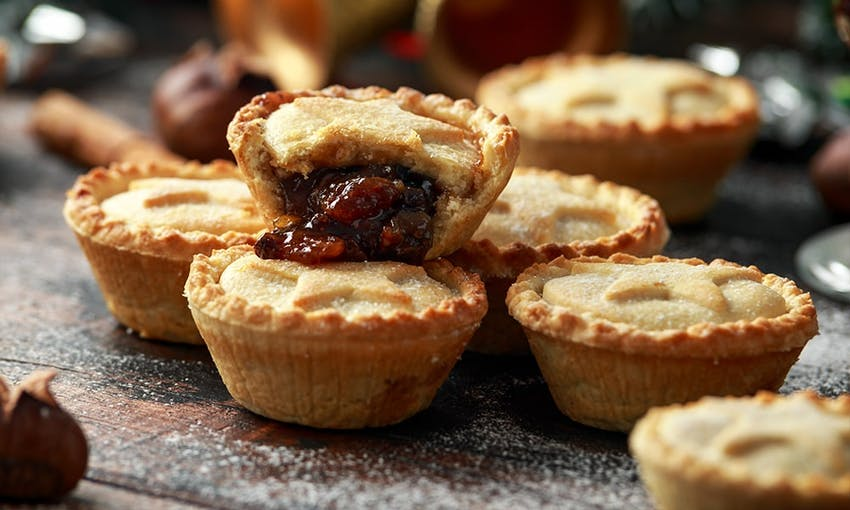 a stack of mince pies  on a dark wooden table with a dusting of icing sugar