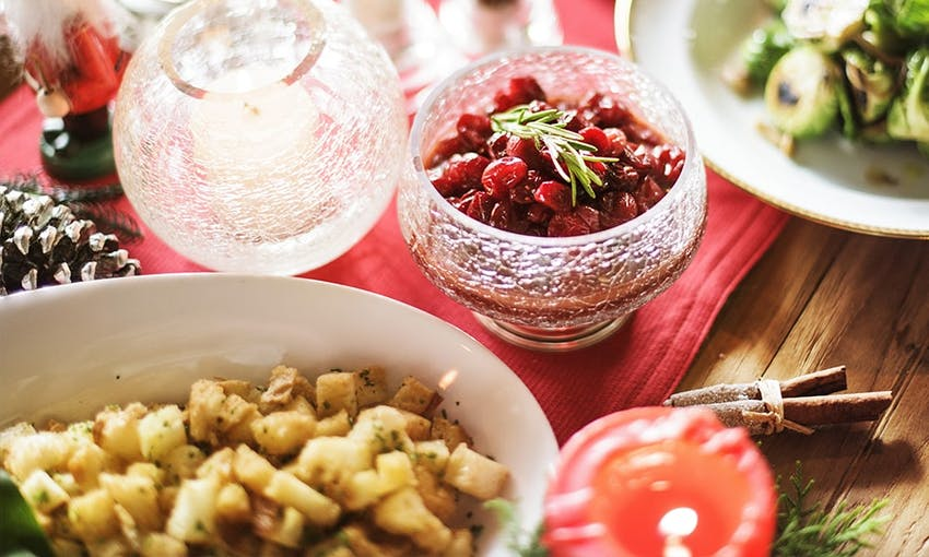 christmas dinner table with lit candle, brussel sprouts, side dishes and cranberry sauce topped with rosemary sprig