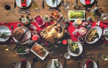 birds eye view of a fully set christmas dinner with a red table runner a turkey centre piece