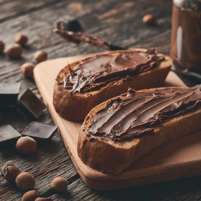 two thick slices of brown bread with a good helping of nutella on a wooden chopping board with dark chocolate pieces and hazelnuts to decorate the table
