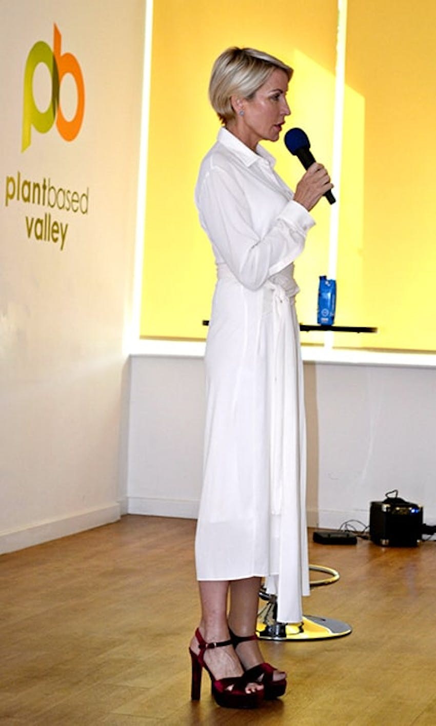 Heather mills speaking into microphone at the launch event of plant based valley dressed in white