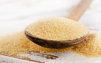 Brown sugar on a wooden spoon with sugar overflowing off spoon onto a wooden table