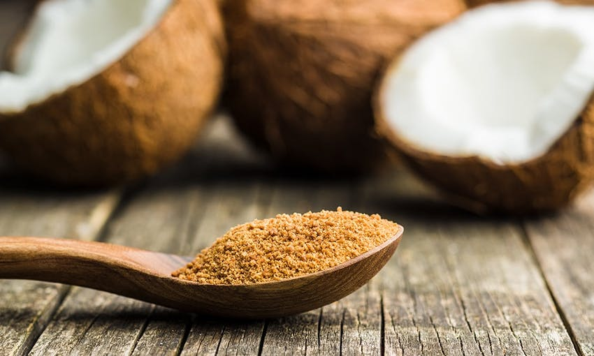 A teaspoon with coconut sugar on a wooden table in front of halved coconuts