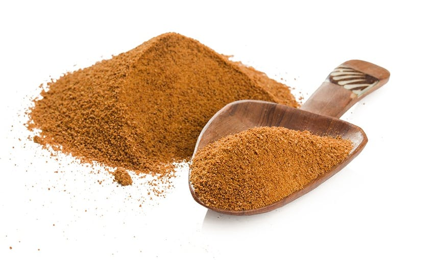 A pile of brown erythritol and a measuring spoon