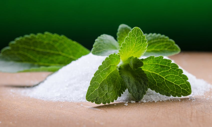 A small mound of stevia on wooden table with stevia leaf placed over the top