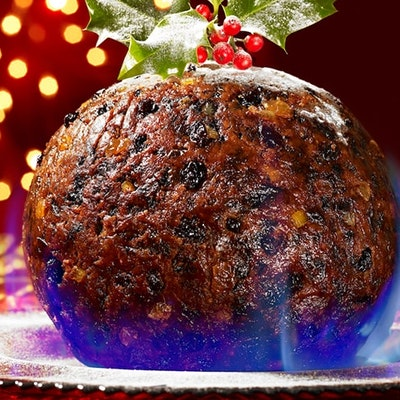 a round flaming christmas pudding on a silver platter on a decorated christmas christmas table with fairy lights in the background