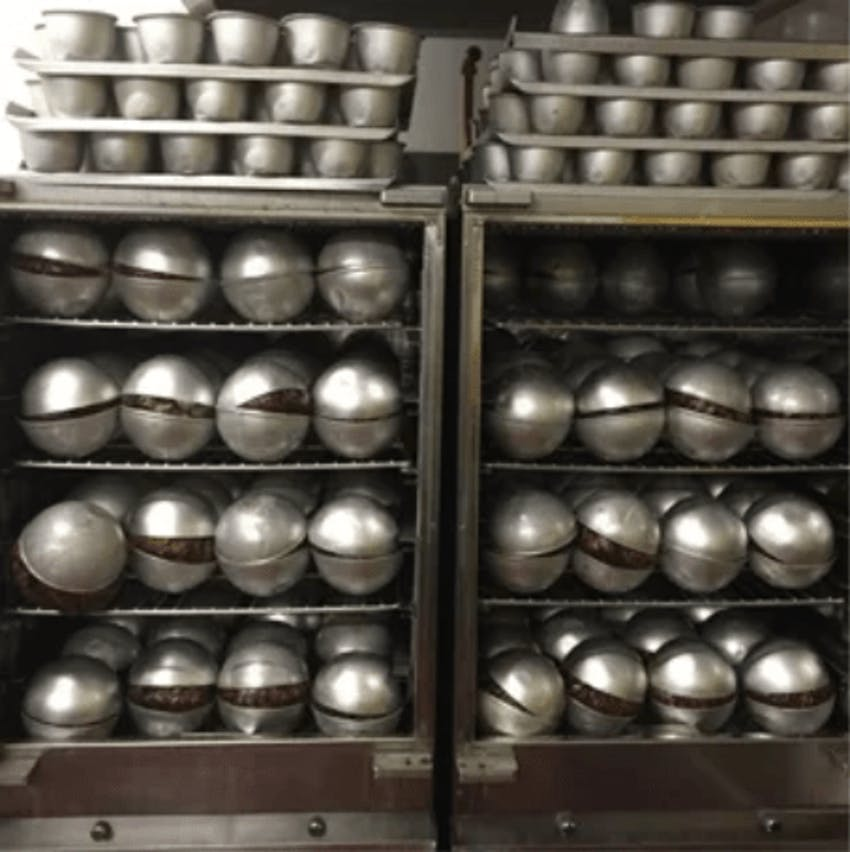 hundreds of georgie porgies christmas puddings in metal casing cooling down in the factory