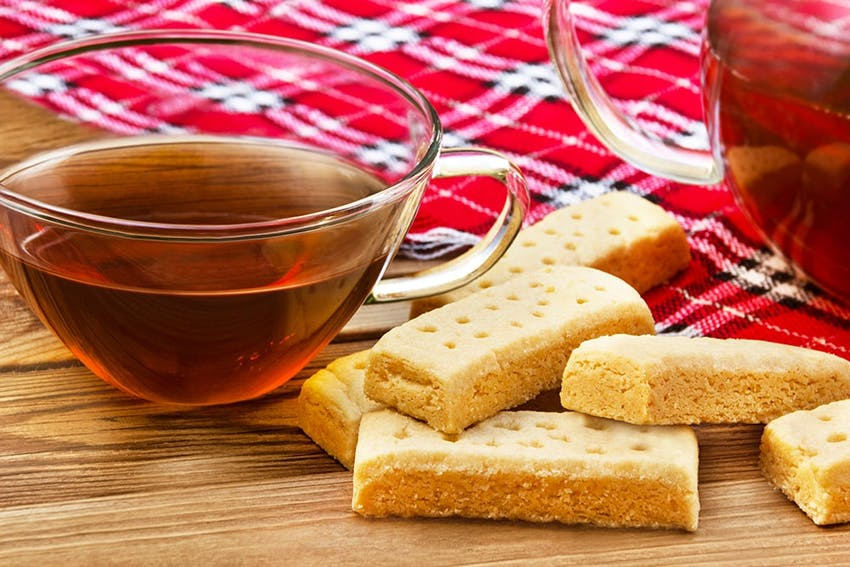 a cup of tea in a clear glass cup next to 6 shortbread fingers laid over a red tartan blanket