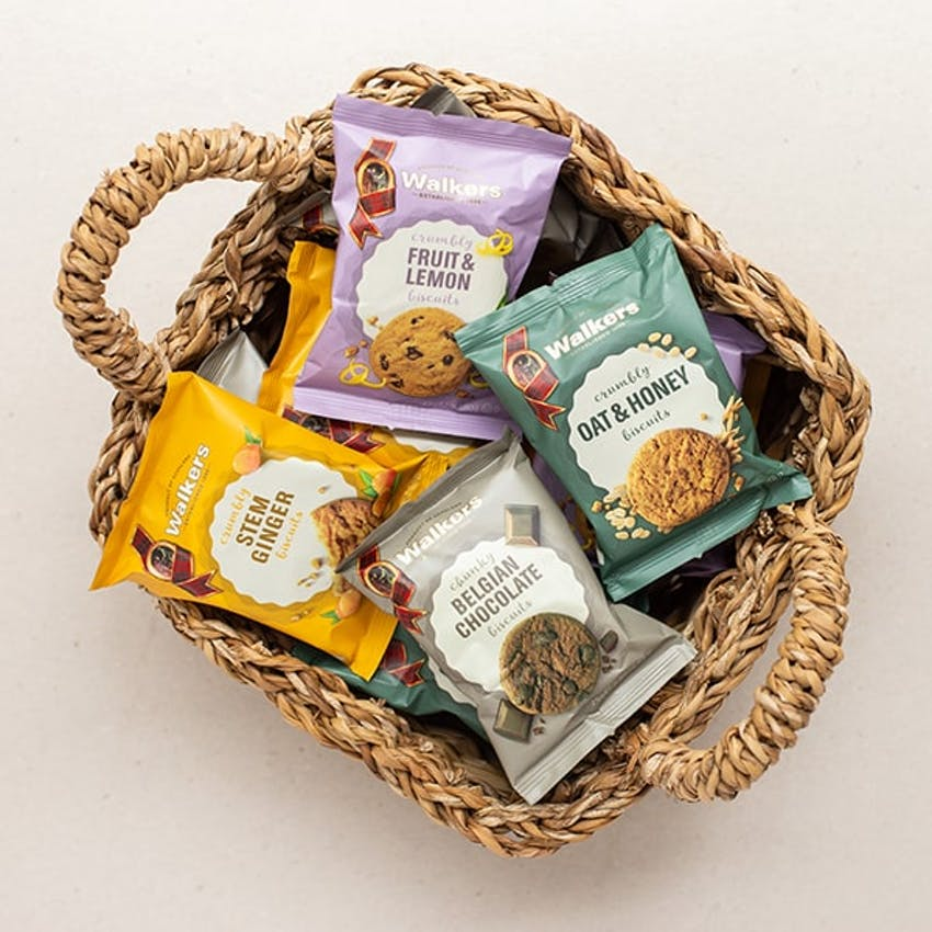 birds eye view of different coloured packets of the different flavours of walkers shortbread in a wicker basket