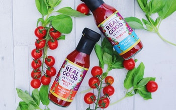 Two bottles of real good ketchup on a white wooden table with tomato plant and vine tomatoes for decoration