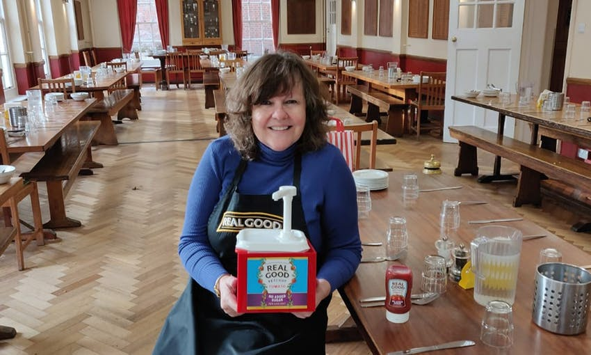 Elizabeth Jones in a large dining hall sat on a bench with a wholesale size of real good ketchup