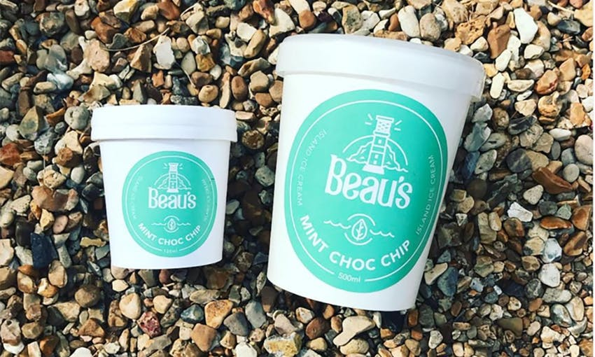 Small White and Blue Beau's Ice Cream Tub next to Large Blue and White Beau's Ice Cream Tub on Pebbled Beach