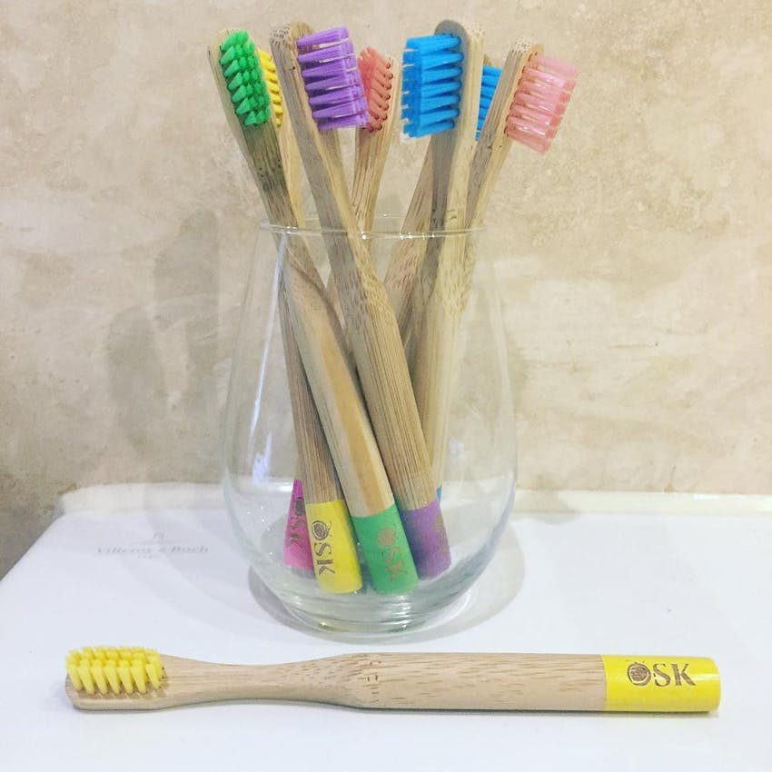 glass jar of different coloured osk eco toothbrushes