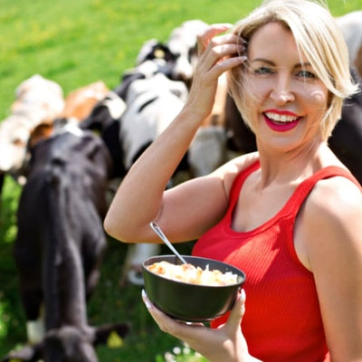 Heather Mills eating a bowl of cereal infront of a group of cows