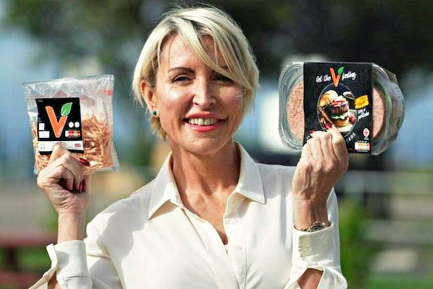 Heather mills smiling whilst holding vbites products in each hand infront of a farmyard background