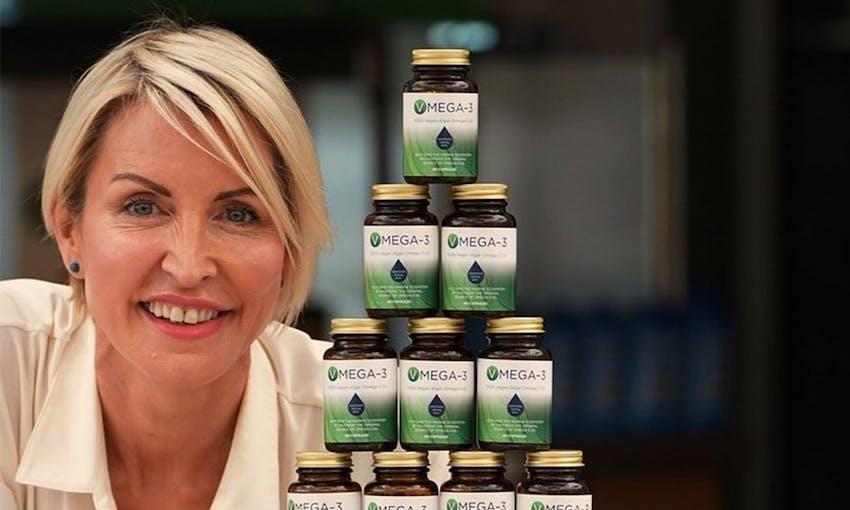 Heather mills smiling next to a stacked pyramid of Vmega 3 Algal Oil