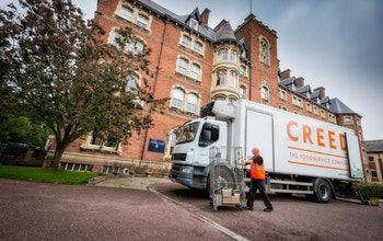 Creed Lorry in front of red brick building with tree