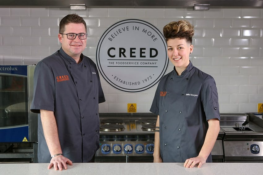 Male and female stood in creed  innovation centre in front of creed 'believe in more' logo