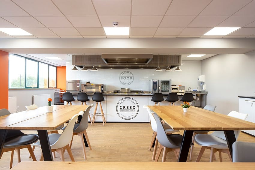 Large wooden dining tables in front of the creed innovation kitchen
