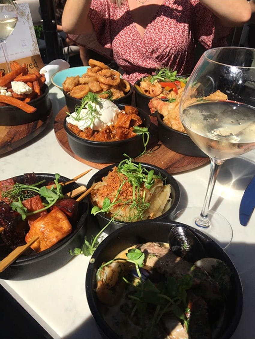 eight small tapas dishes in black bowls accompanied by two glasses of wine