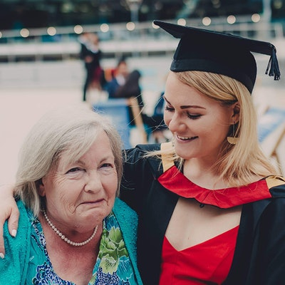 a young girl and her grandma embracing at graduation ceremony