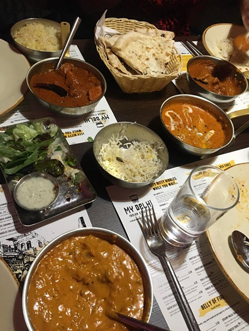 varying plates and trays of indian dishes