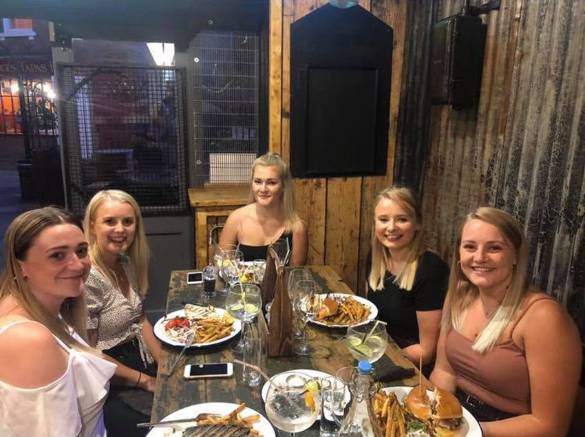 five girls sit around a wooden table in a restaurant smiling for the camera with plates full of food