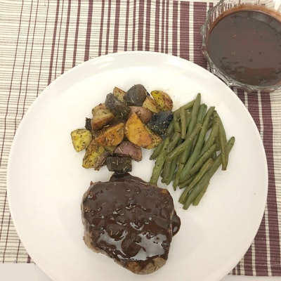 a white plate with steak covered in chocolate and coffee sauce, green beans and roasted vegetables