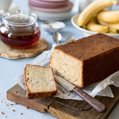 baked banana bread cake with one slice cut off and a silver knife on top of a wooden chopping board