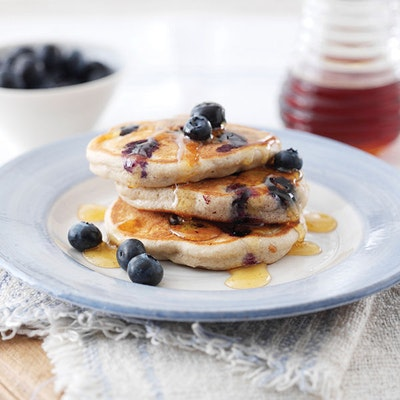 a stack of three pancakes topped with fresh blueberries and drizzled with maple syrup