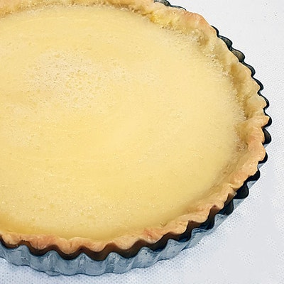 lemon tart dusted with sugar and in a grey latticed baking dish