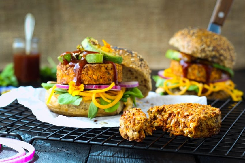 two burger buns filled with lentil and mixed seeds burgers, avocado, sauce and salad on a wire cooling rack
