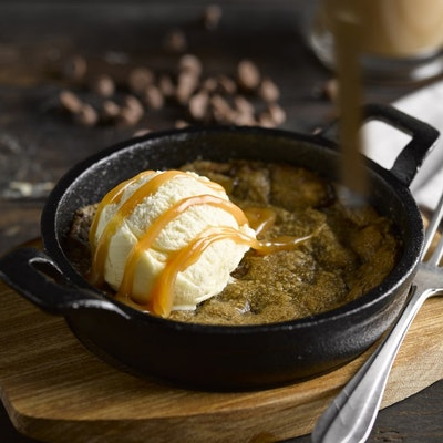 black skillet with warm cookie dough with a scoop of vanilla ice cream and chocolate sauce drizzled on top