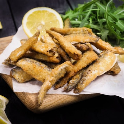 paramount msc coated whitebait fish on a wooden chopping board served with salad and sliced lemons