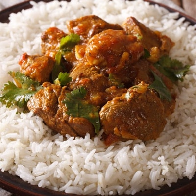 rogan josh lamb curry on a bed of white fluffy rice