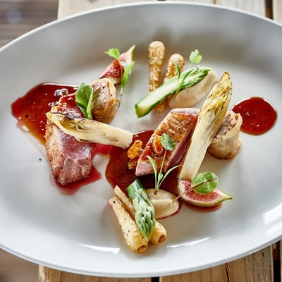 an a la carte style dish of duck breast, charred chicory and figs drizzled with fig and date jus