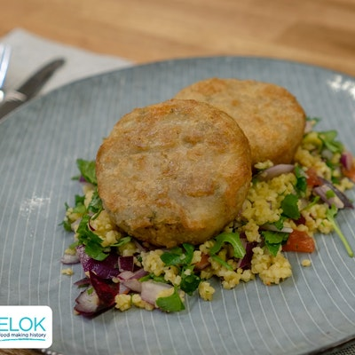 two crispy pollock fishcakes on a bed of Moroccan tabbouleh on a grey plate