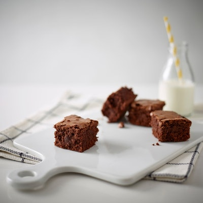 chunks of brownie on a glossy white chopping board next to a glass of milk with a yellow and white straw