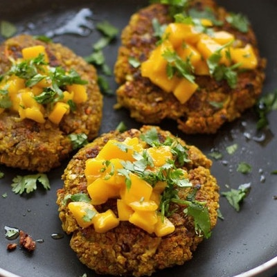three crispy vegan burgers topped with fresh herbs and served on a plate