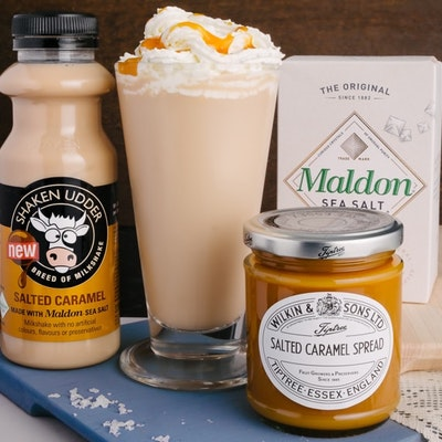 shaken udder salted caramel milkshake and wilkin and sons salted caramel spread next to a tall glass of salted caramel hot chocolate