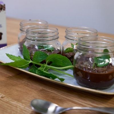 a rectangle plate with four small cheesecakes in glass jars displayed with fresh mint