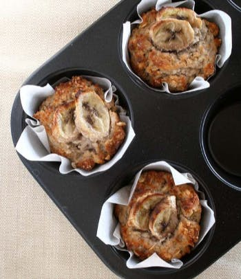 Three golden brown cooked banana muffins in a muffin tray lined with baking paper