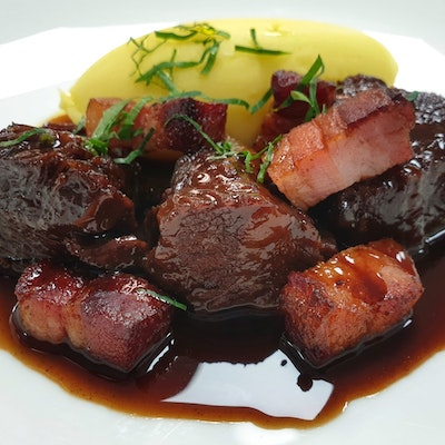 Braised Beef in a Red Wine and Port jus with creamy mash potato topped with fresh herbs